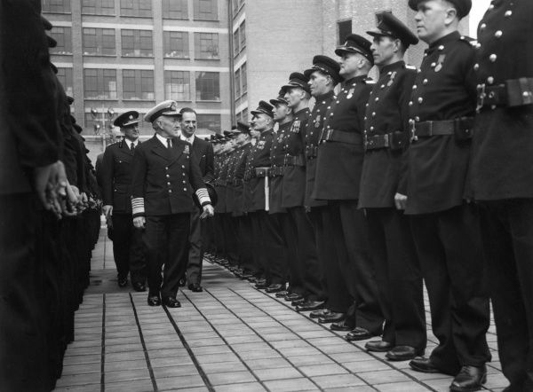 An Admiral inspecting firefighters wearing medals, London