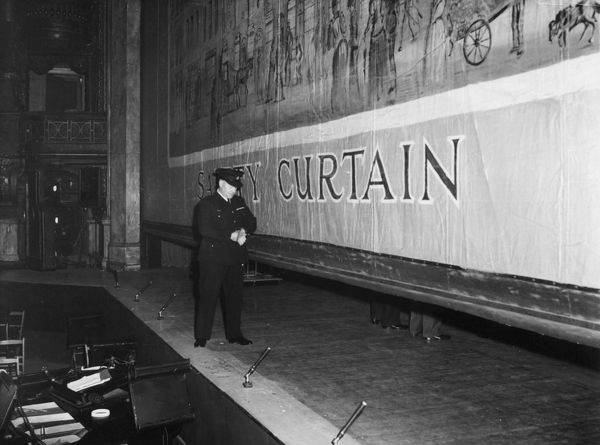 A fire prevention officer checking the time it takes for a safety curtain to come down on a theatre stage. It should not take longer than 30 seconds