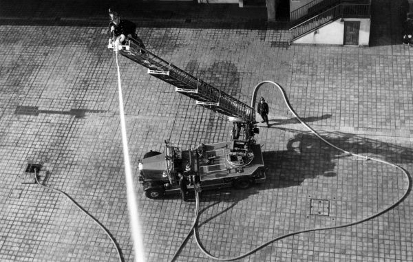 Firefighter training at the London Fire Brigade HQ in Lambeth, with a man operating a hose at the top of the turntable ladder. Aerial view, probably taken from the top of the drill tower