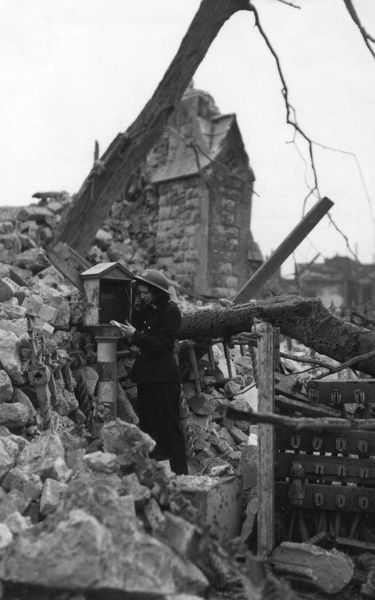 A firefighter making a call from a working fire alarm outside a ruined church during the Second World War