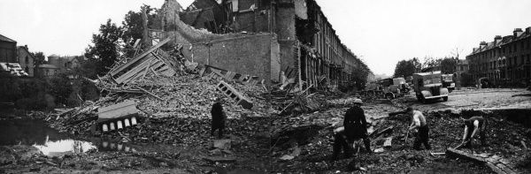 Panoramic view of extensive bomb damage and a crater in Petherton Road, North London, 2 July 1944. A salvage operation took place, pumping out flooded basements