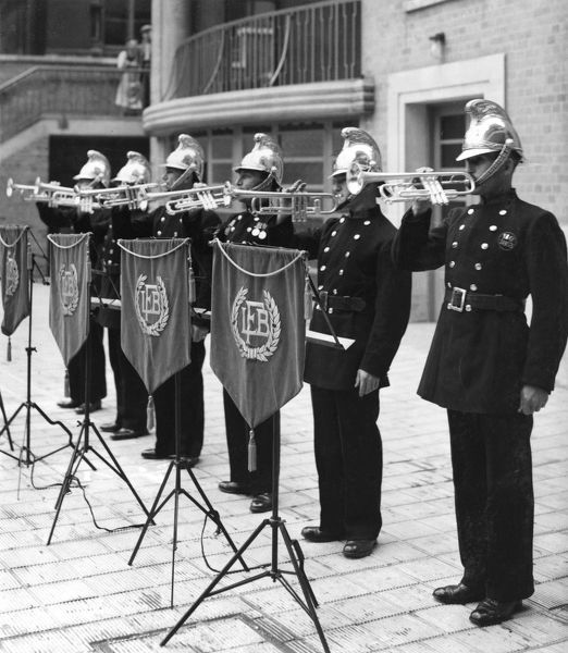 Members of the LCC-London Fire Brigade band, standing in a row playing their instruments