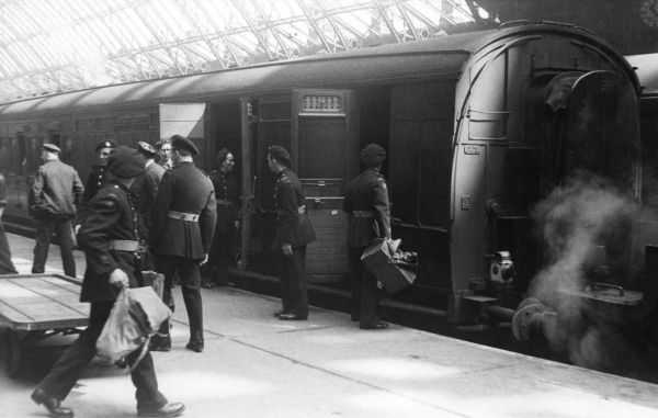 NFS personnel helping to load luggage from a trolley onto a train at St Pancras railway station, 14 July 1944, as part of an evacuation exercise during a period of bombing