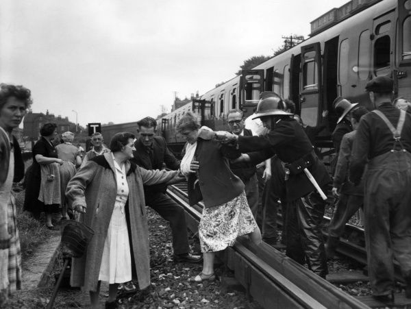 Train collision and derailment at Maze Hill Station, SE London, 4 July 1958. Showing injured passengers being helped across the tracks to waiting ambulances