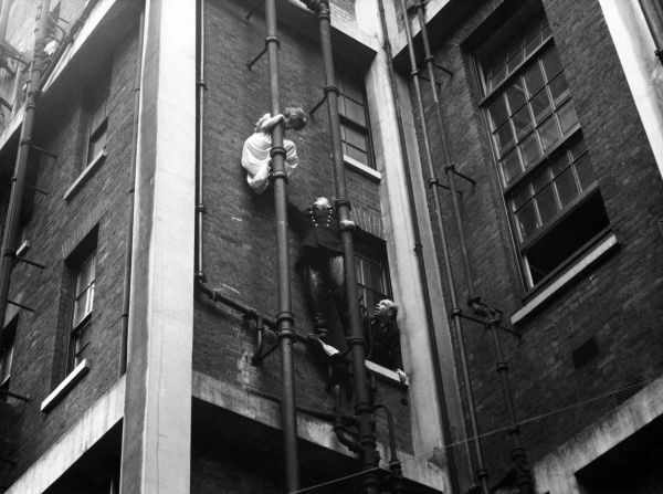 LFB Special Services trying to help a woman patient at St Mary's Hospital, Paddington, London, on 15 April 1959. She has climbed out of a ward window at fifth floor level and is sitting with her feet on a tie rod of the drainpipe