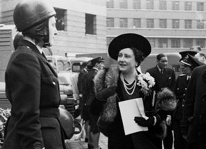 Queen Elizabeth reviews a female dispatch rider of the LFB.