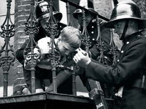 Firefighter releasing boy with head stuck in railings LFB150